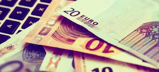 Steuerberater Gehalt - Geldscheine auf Laptop Tastatur