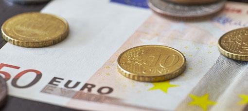 Steuerberater Kosten - Geldscheine und Münzen auf einem Tisch