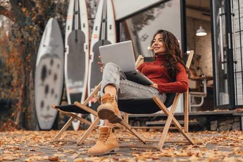 Frau in gemütlicher Umgebung arbeitet bei Laptop während des Sitzens auf dem Stuhl in der Nähe des Cafés im Herbstpark