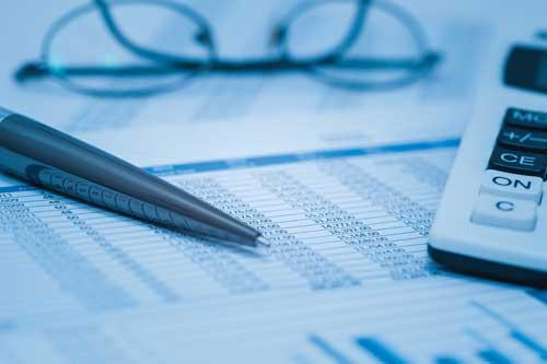 Buchhaltungs-Tabellen mit Brillen und Taschenrechner in Blau. Nahaufnahme-Konzept für Stock-, Bank- und Buchführungsdaten.